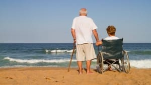 Elder couple on beach man with cane woman in wheelchair